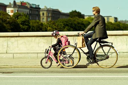 Pai e filha passeiam de bicicleta na Dinamarca