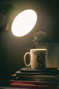 Uma caneca de café sobre uma pilha de livros iluminada por uma luminária.
